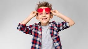 Ένα όμορφο αγόρι σε ένα πουκάμισο καρό, το γκρίζα πουκάμισο και τα τζιν στέκεται σε ένα γκρίζο υπόβαθρο Ένα αγόρι στα κόκκινα γυα Στοκ Φωτογραφία