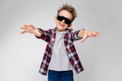 Ένα όμορφο αγόρι σε ένα πουκάμισο καρό, το γκρίζα πουκάμισο και τα τζιν στέκεται σε ένα γκρίζο υπόβαθρο Το αγόρι στα μαύρα γυαλιά Στοκ εικόνα με δικαίωμα ελεύθερης χρήσης