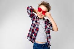 Ένα όμορφο αγόρι σε ένα πουκάμισο καρό, το γκρίζα πουκάμισο και τα τζιν στέκεται σε ένα γκρίζο υπόβαθρο Ένα αγόρι στα κόκκινα γυα Στοκ Εικόνες