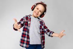 Ένα όμορφο αγόρι σε ένα πουκάμισο καρό, το γκρίζα πουκάμισο και τα τζιν στέκεται σε ένα γκρίζο υπόβαθρο Ένα αγόρι στα κόκκινα ακο Στοκ εικόνες με δικαίωμα ελεύθερης χρήσης