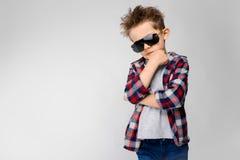 Ένα όμορφο αγόρι σε ένα πουκάμισο καρό, το γκρίζα πουκάμισο και τα τζιν στέκεται σε ένα γκρίζο υπόβαθρο Το αγόρι στα μαύρα γυαλιά Στοκ Εικόνα