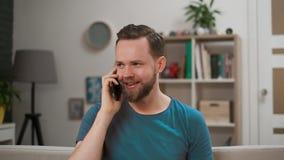 Ένα όμορφο αρσενικό μιλά στο τηλέφωνο και χαμογελά στο σπίτι Το πορτρέτο του ευτυχούς γενειοφόρου ατόμου έντυσε περιστασιακό εσωτ απόθεμα βίντεο