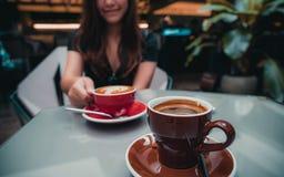 Ένα όμορφο ασιατικό φλυτζάνι καφέ εκμετάλλευσης γυναικών latte με το φλυτζάνι καφέ Americano στον πίνακα γυαλιού στον καφέ σοφιτώ Στοκ φωτογραφία με δικαίωμα ελεύθερης χρήσης