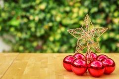 Ένα όμορφο αστέρι Χριστουγέννων που περιβάλλεται από μερικές κόκκινες σφαίρες Χριστουγέννων Στοκ Εικόνες