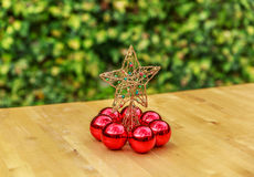 Ένα όμορφο αστέρι Χριστουγέννων που περιβάλλεται από τις κόκκινες σφαίρες Στοκ Φωτογραφίες