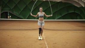 Ένα όμορφο, γενναίο κορίτσι ασκεί σκληρά με ένα πηδώντας σχοινί σε ένα γήπεδο αντισφαίρισης Στο δεξί πόδι η πρόσθεση είναι απόθεμα βίντεο
