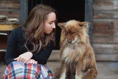 Ένα όμορφο ευρωπαϊκό κορίτσι κάθεται στο μέρος με ένα χνουδωτό σκυλί ποιμένων ` s Στοκ Φωτογραφία