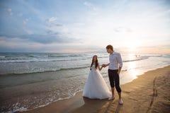 Ένα όμορφο ζεύγος των newlyweds, η νύφη και ο νεόνυμφος που περπατούν στην παραλία Πανέμορφο ηλιοβασίλεμα και ουρανός Γαμήλια φορ στοκ εικόνα