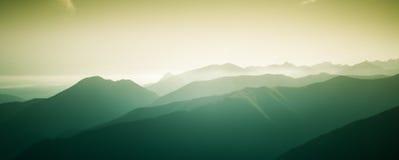 Ένα όμορφο, ζωηρόχρωμο, αφηρημένο τοπίο βουνών με μια καυτή θερινή ελαφριά ομίχλη στη θερμή πράσινη τονικότητα Στοκ φωτογραφίες με δικαίωμα ελεύθερης χρήσης