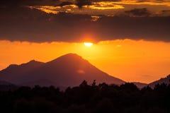 Ένα όμορφο, ζωηρόχρωμο ηλιοβασίλεμα πέρα από τα βουνά, λίμνη και δάσος στους πορφυρούς τόνους Αφηρημένο, φωτεινό τοπίο στοκ εικόνες