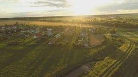 Ένα όμορφο ηλιοβασίλεμα πέρα από το ρωσικό χωριό Τομείς και δέντρα γύρω Εναέριος και τηλεοπτικός πυροβολισμός απόθεμα βίντεο