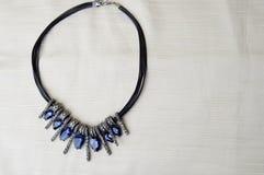 Ένα όμορφο, θηλυκό, μοντέρνο περιδέραιο σε μια μαύρη λαστιχένια ζώνη με τους μπλε λάμποντας πολύτιμους λίθους, διαμάντια ενάντια  Στοκ Φωτογραφίες