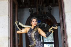 Ένα όμορφο ισπανικό πρότυπο Brunette θέτει με ένα Boa φίδι σφιγκτήρων γύρω από το σώμα της στοκ εικόνα