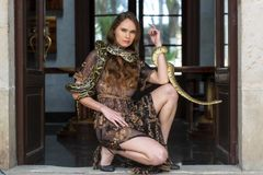 Ένα όμορφο ισπανικό πρότυπο Brunette θέτει με ένα Boa φίδι σφιγκτήρων γύρω από το σώμα της στοκ εικόνες