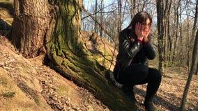 Ένα όμορφο κορίτσι κάθεται κάτω από ένα μεγάλο δέντρο Το κορίτσι χάθηκε φιλμ μικρού μήκους