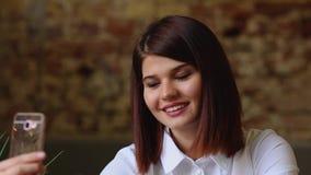 Ένα όμορφο κορίτσι κάθεται σε έναν καφέ και μετά από πιωμένος ένα καυτό coffe, θέτει για μια κινητή τηλεφωνική κάμερα για να κάνε απόθεμα βίντεο