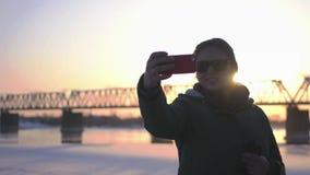 Ένα όμορφο κορίτσι κάνει selfie σε ένα υπόβαθρο ηλιοβασιλέματος και μια γέφυρα με έναν σιδηρόδρομο 4K απόθεμα βίντεο
