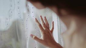 Ένα όμορφο κορίτσι κοιτάζει μέσω του παραθύρου ήπια σχετικά με το Tulle απόθεμα βίντεο