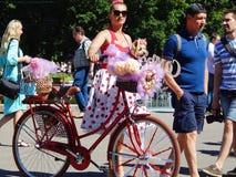 Ένα όμορφο κορίτσι με ένα σκυλί κατοικίδιων ζώων στις κυρίες παρελάσεων ` στα ποδήλατα Στοκ εικόνες με δικαίωμα ελεύθερης χρήσης
