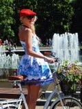 Ένα όμορφο κορίτσι με την κόκκινη ΚΑΠ στις κυρίες παρελάσεων ` στα ποδήλατα Στοκ Φωτογραφίες
