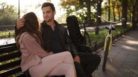 Ένα όμορφο κορίτσι με τη μακριά καφετιά τρίχα κάθεται το αγκάλιασμα με τον όμορφο τύπο brunette της σε έναν πάγκο πάρκων Πορτρέτο απόθεμα βίντεο