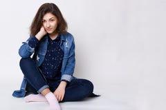 Ένα όμορφο κορίτσι με τη σκοτεινή τρίχα και τα γοητευτικά καφετιά μάτια που φορούν μοντέρνο Jean ντύνει τα κάθισμα διασχισμένα πό Στοκ φωτογραφίες με δικαίωμα ελεύθερης χρήσης