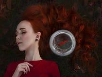 Ένα όμορφο κορίτσι με τους μακροχρόνιους κόκκινους ύπνους τρίχας δίπλα σε ένα goldfish σε ένα ενυδρείο Νέα κοκκινομάλλης γυναίκα  στοκ φωτογραφία