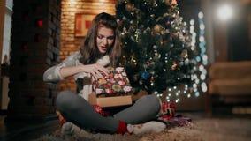 Ένα όμορφο κορίτσι μια συνεδρίαση χριστουγεννιάτικου δώρου στο πάτωμα σε ένα καλά-διακοσμημένο καθιστικό φιλμ μικρού μήκους