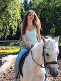 Ένα όμορφο κορίτσι οδηγά ένα όμορφο άσπρο άλογο Στοκ Φωτογραφία