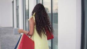 Ένα όμορφο κορίτσι περιστρέφει με τις συσκευασίες μετά από να ψωνίσει με μια καλή διάθεση 4K φιλμ μικρού μήκους