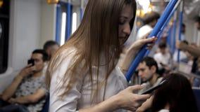 Ένα όμορφο κορίτσι πηγαίνει στον υπόγειο, κρατά το κιγκλίδωμα και χρησιμοποιεί το τηλέφωνο φιλμ μικρού μήκους
