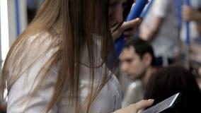 Ένα όμορφο κορίτσι πηγαίνει στον υπόγειο, κρατά το κιγκλίδωμα και χρησιμοποιεί το τηλέφωνο απόθεμα βίντεο