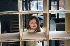 Ένα όμορφο κορίτσι που κοιτάζει έξω από πίσω από μια κλουβί-διαμορφωμένη δομή Έννοια παιχνιδιού στοκ εικόνα