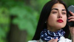 Ένα όμορφο κορίτσι σε ένα άσπρο αδιάβροχο χρωματίζει τα χείλια της με το κραγιόν φιλμ μικρού μήκους
