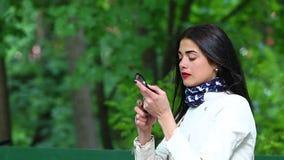 Ένα όμορφο κορίτσι σε ένα άσπρο αδιάβροχο χρωματίζει τα χείλια της με το κραγιόν απόθεμα βίντεο