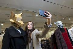 Ένα όμορφο κορίτσι σε ένα κατάστημα με τα ενδύματα παίρνει τις εικόνες της στο τηλέφωνο δίπλα στα μανεκέν με ένα ζωικό κεφάλι στοκ φωτογραφίες