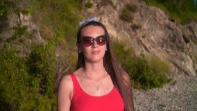 Ένα όμορφο κορίτσι σε ένα κόκκινο ενός κομματιού μαγιό και τα γυαλιά στέκεται στην ακτή σε ένα κλίμα των πράσινων δέντρων απόθεμα βίντεο