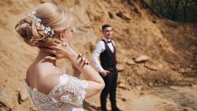 Ένα όμορφο κορίτσι σε ένα λευκό σαν το χιόνι φόρεμα τρέχει ήπια τα δάχτυλά της κατά μήκος του λαιμού της Στέκεται στα πλαίσια των φιλμ μικρού μήκους
