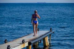 Ένα όμορφο κορίτσι σε ένα μπλε μπικίνι περπατά την αποβάθρα στη θάλασσα Θαλάσσια συγκεκριμένη αποβάθρα Άλμα στο νερό από την αποβ στοκ φωτογραφίες