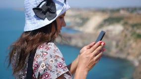 Ένα όμορφο κορίτσι στέκεται σε μια κλίση θαλασσίως και γράφει ένα μήνυμα στο τηλέφωνο HD, 1920x1080 κίνηση αργή απόθεμα βίντεο