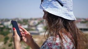 Ένα όμορφο κορίτσι στέκεται στην οδό το καλοκαίρι και γράφει ένα μήνυμα στο τηλέφωνο HD, 1920x1080 κίνηση αργή απόθεμα βίντεο