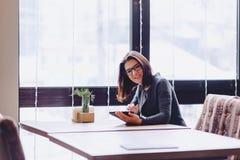 Ένα όμορφο κορίτσι στα γυαλιά εργάζεται σε ένα τραπεζάκι σαλονιού Στοκ εικόνα με δικαίωμα ελεύθερης χρήσης