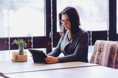 Ένα όμορφο κορίτσι στα γυαλιά εργάζεται σε ένα τραπεζάκι σαλονιού Στοκ Εικόνες