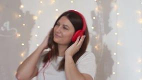 Ένα όμορφο κορίτσι στις πυτζάμες χαλαρώνει το άκουσμα στη μουσική στα ακουστικά καθμένος στο κρεβάτι σε μια καλή διάθεση Κινηματο φιλμ μικρού μήκους