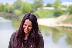 Ένα όμορφο κορίτσι χωρίς makeup με τη μακριά σκοτεινή τρίχα που γελά κοντά στον ποταμό Στοκ εικόνες με δικαίωμα ελεύθερης χρήσης
