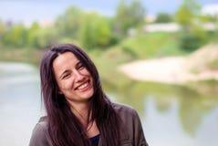 Ένα όμορφο κορίτσι χωρίς makeup με τη μακριά σκοτεινή τρίχα που γελά κοντά στον ποταμό Στοκ Εικόνες