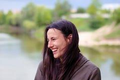 Ένα όμορφο κορίτσι χωρίς makeup με τη μακριά σκοτεινή τρίχα που γελά κοντά στον ποταμό Στοκ Φωτογραφία