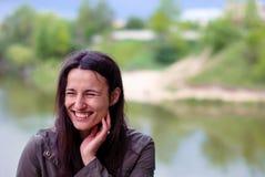 Ένα όμορφο κορίτσι χωρίς makeup με τη μακριά σκοτεινή τρίχα που γελά κοντά στον ποταμό Στοκ Φωτογραφίες