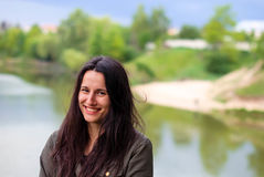 Ένα όμορφο κορίτσι χωρίς makeup με τη μακριά σκοτεινή τρίχα που γελά κοντά στον ποταμό Στοκ φωτογραφίες με δικαίωμα ελεύθερης χρήσης