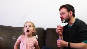 Ένα όμορφο κοριτσάκι πιάνει τις φυσαλίδες σαπουνιών από το στόμα της Ένας πατέρας και η κόρη του ξοδεύουν το χρόνο από κοινού φιλμ μικρού μήκους